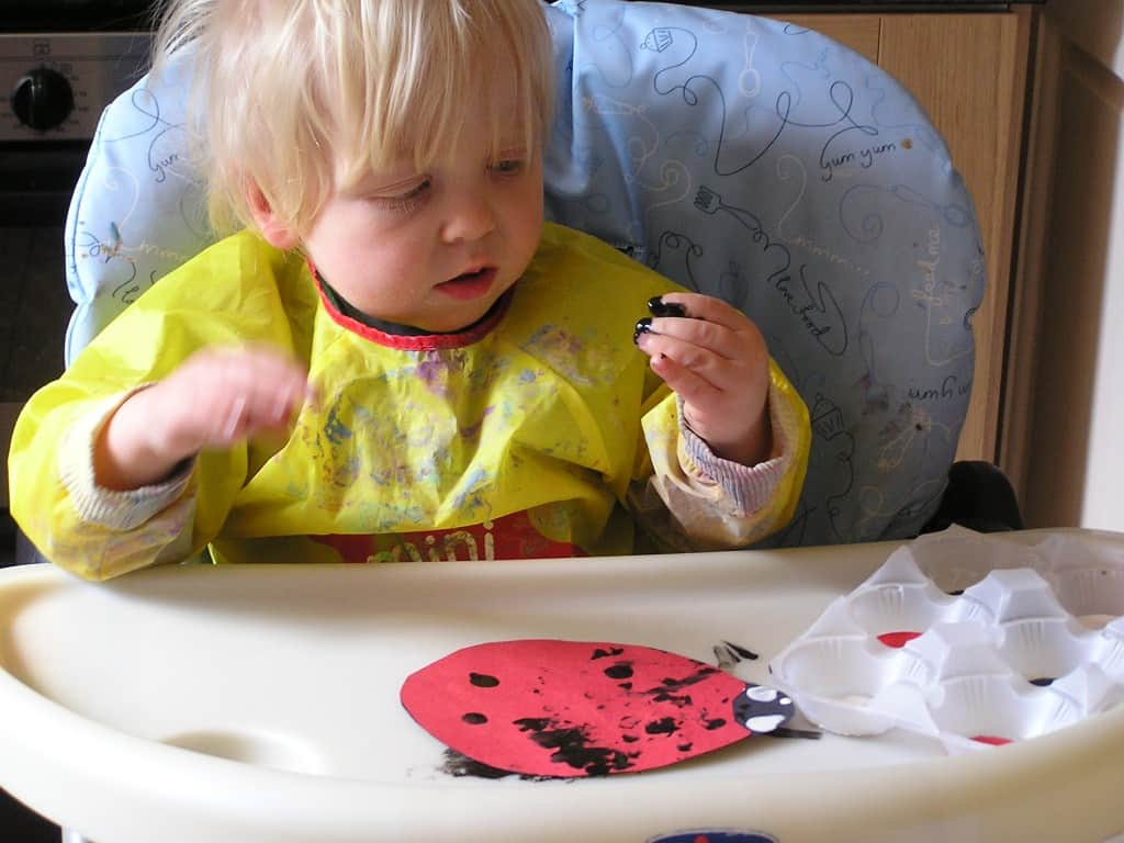 toddler making art in a high tray