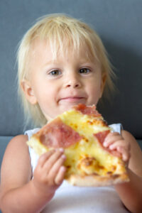 toddler eating homemade pizza on the sofa