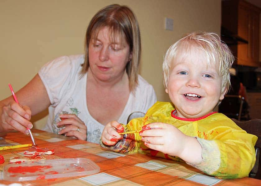 mum joining in with toddler at the kitchen table painting and crafting