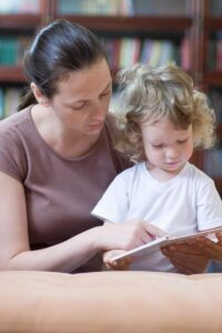 mother and toddler at the library helping the toddler to learn to love books and encourage reading from an early age
