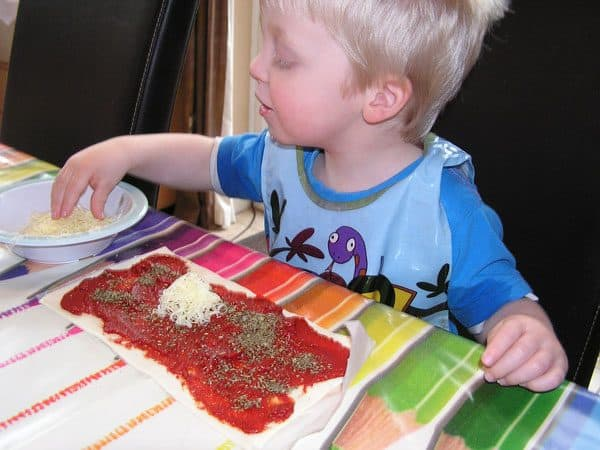 toddler sprinkling cheese on pizza