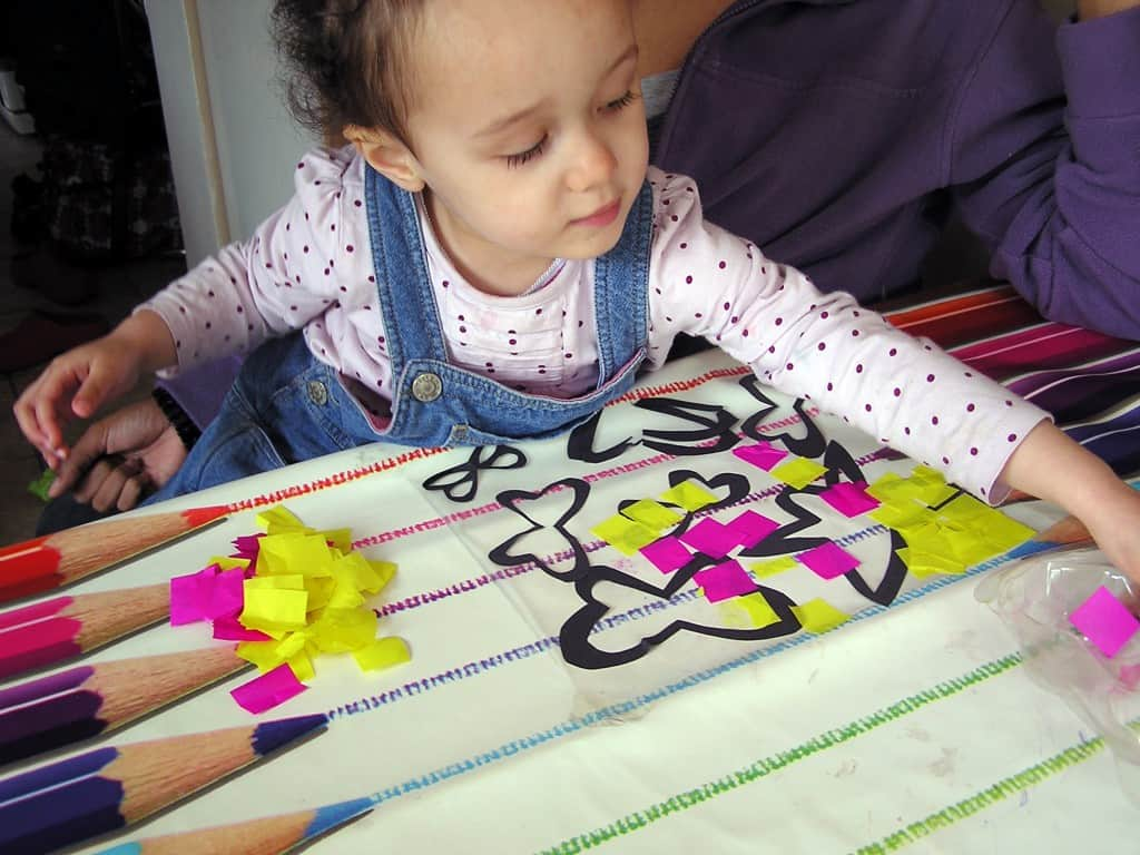 toddler creating a stained glass butterfly picture with black cut out butterflies and pink and yellow tissue paper