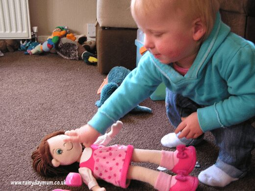 giving doll some tea imaginative play