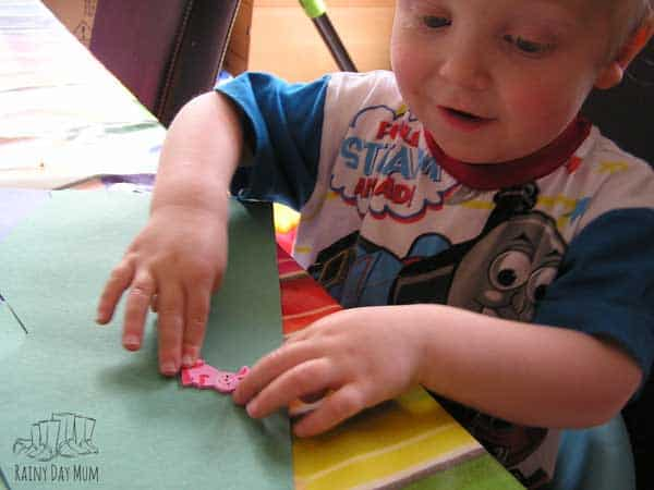 toddler boy putting an animal sticker on a piece of green paper