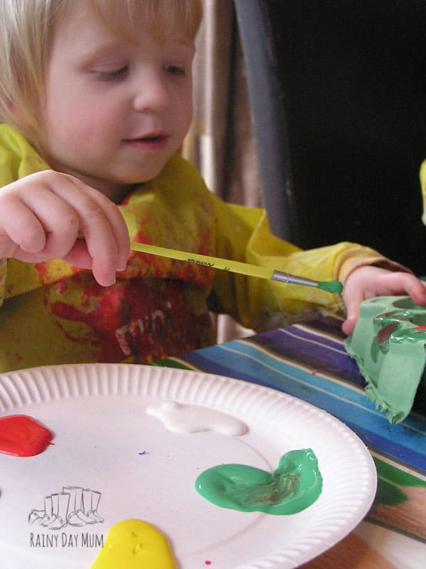 toddler painting egg boxes to create egg box caterpillars that will then grow