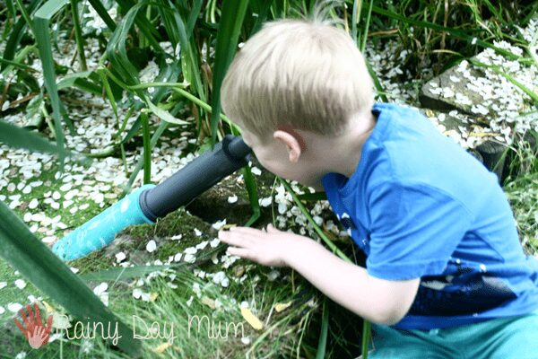 child using the underwater scope from learning resources to see under the water in a pond