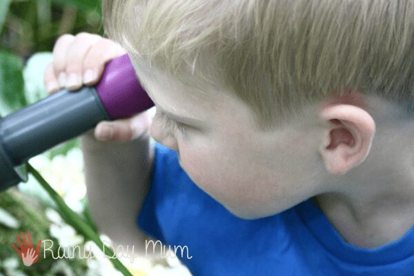 close up of child holding an underwater scope to their eye to view what is happening under the water in the pond.