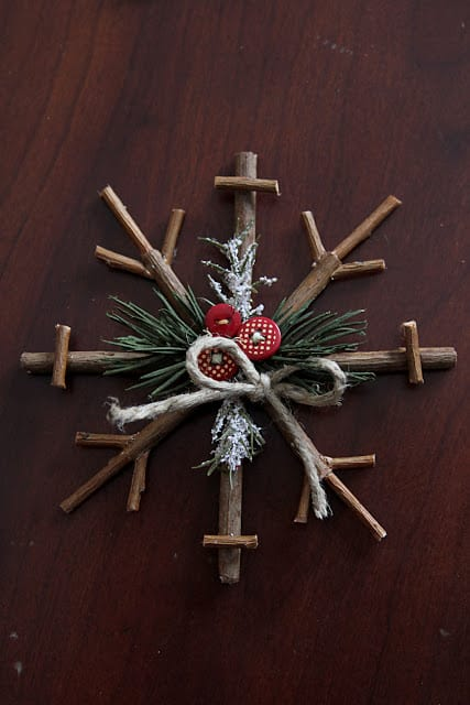 simple ornament for the christmas tree made from twigs with twine, buttons and pine needles