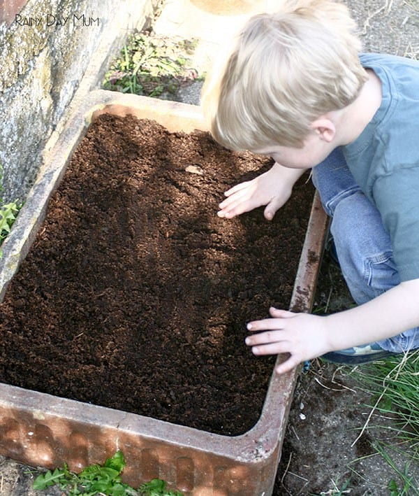 toddler planting seeds in an old sink
