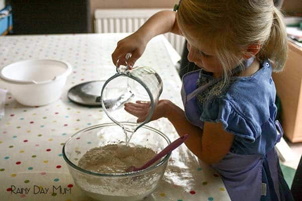preschooler making bread at the kitchen table pouring water into a bowl full of flour