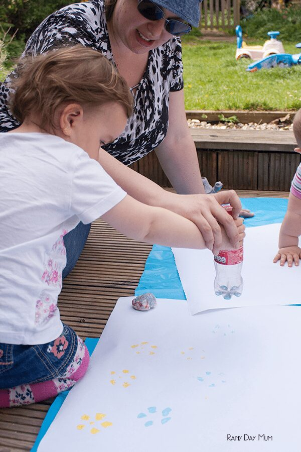 toddler having help from a parent to create prints with a plastic bottle
