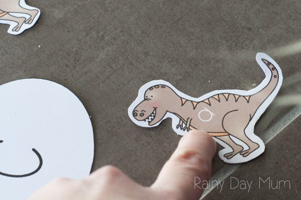 pointing out a lower case a on a dino baby with this letter game for preschoolers
