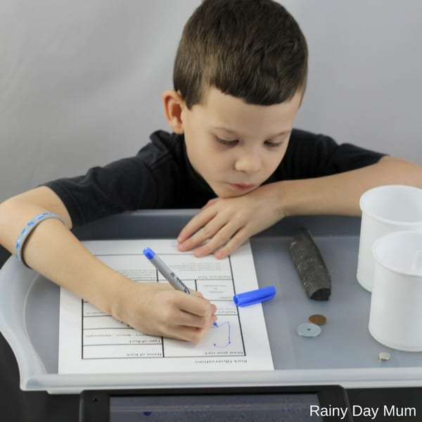 child filling in a rock testing worksheet whilst studying rocks in homeschool