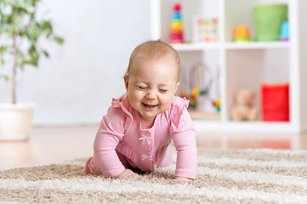 8-month-old baby girl crawling and laughing whilst playing games with her parents