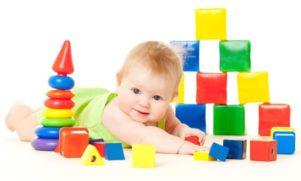 Little 5-month-old baby surrounded by simple none electronic toys ideal for starting to introduce at this age range