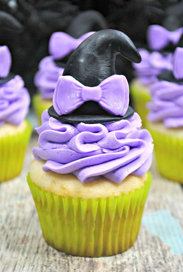 Witches hat cupcake in focus with lilac buttercream frosting