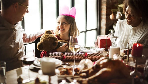 Family sitting down to celebrate Christmas Eve together at the table with delicious and simple family meal ideas