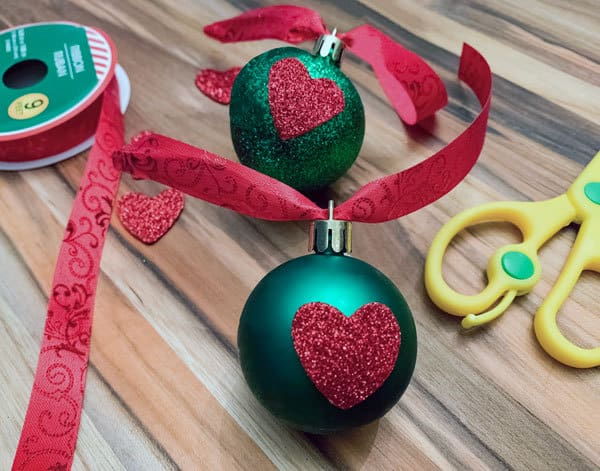 simple christmas decorations to create with kids inspired by the movie and book how the grinch stole christmas - adding the ribbon to hang