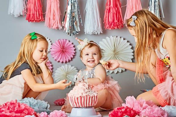 baby girl celebrating first birthday with siblings and mum