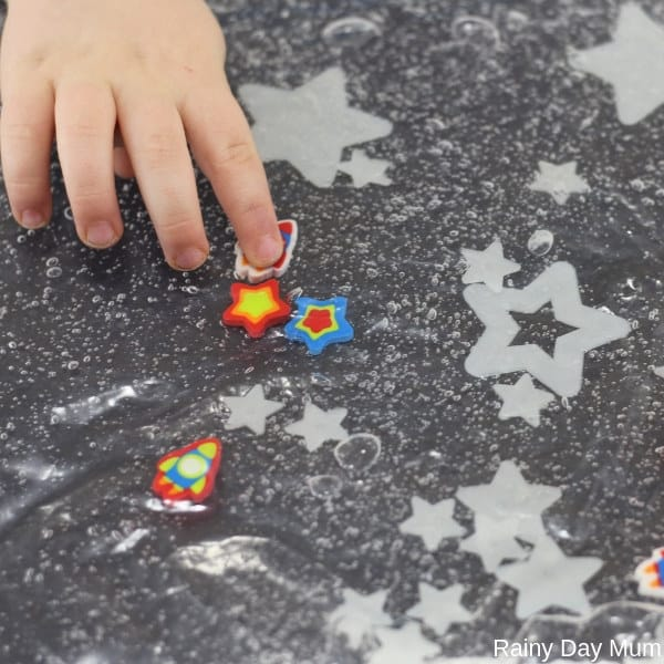 toddler playing with a glow in the dark space themed sensory bag taking the rocket to the different sized stars