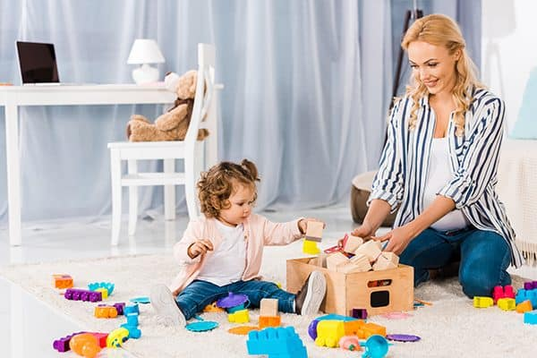 mother and toddler putting their toys away