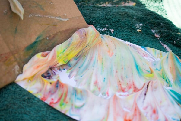removing shaving foam from paper a step in the process of creating shaving foam marbling with kids