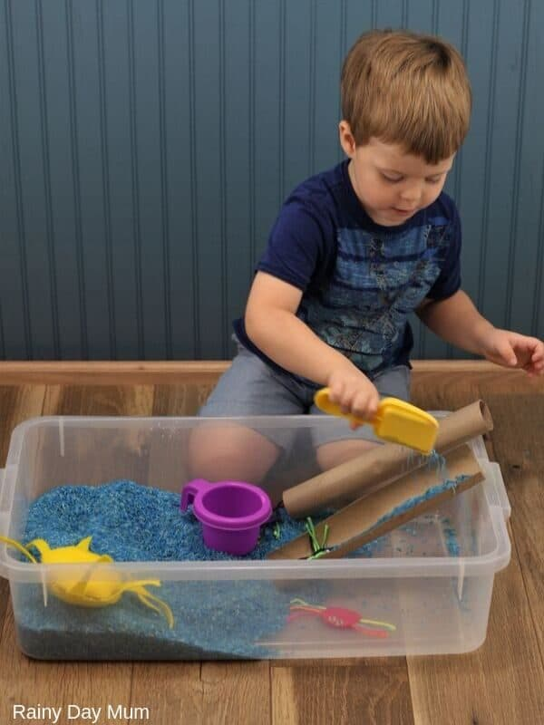 toddler pouring blue coloured rice down a cardboard tube to represent the rain coming down the water spout in Incy Wincy Spider Nursery Rhyme