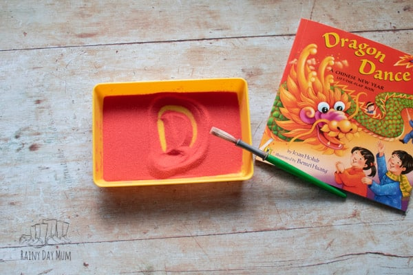 chinese new year writing the letter D from the front cover of Dragon Dance in a sand tray