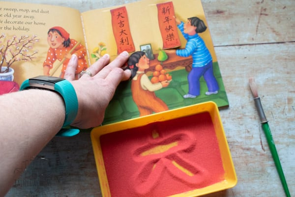 Copying Chinese Symbols from the Dragon Dance Book to write in the sand tray