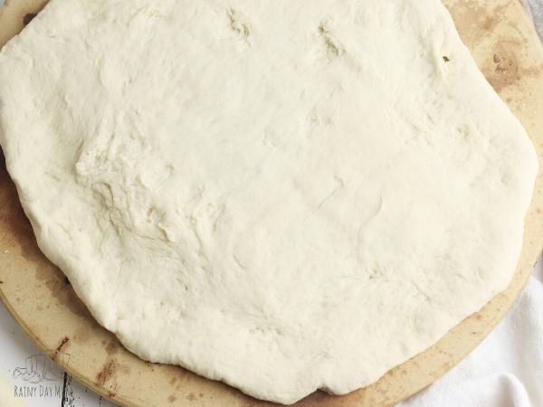 Rolled out pizza dough ready to be baked before adding the toppings