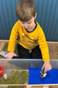 toddler playing in an old MacDonald Farm Sensory Bin