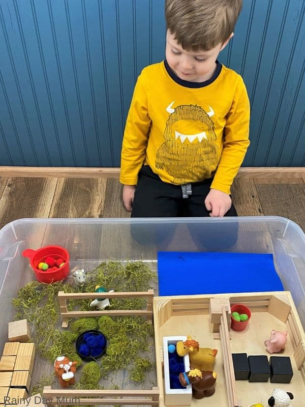 inviting a toddler to play with the simple sensory play farm in an under bed storage bin