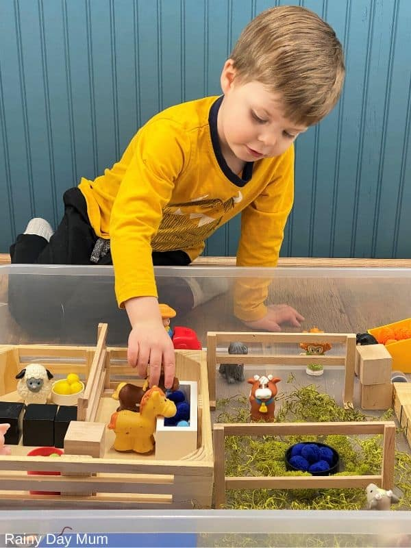 toddler playing with a horse in a farm sensory bin