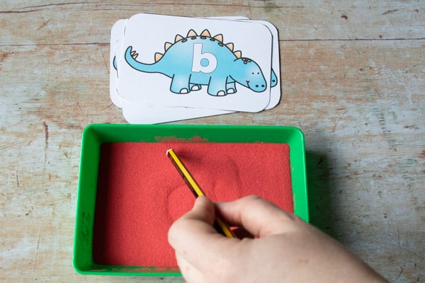 using the end of a pencil to write in the sand tray