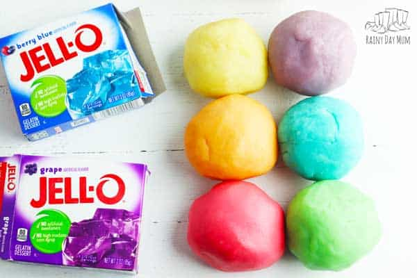 balls of colourful play dough made with jell-o alongside 2 boxes of the jell-o