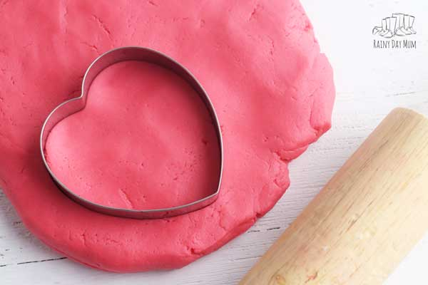 red cherry playdough with a heart cutter and rolling pin ready for play