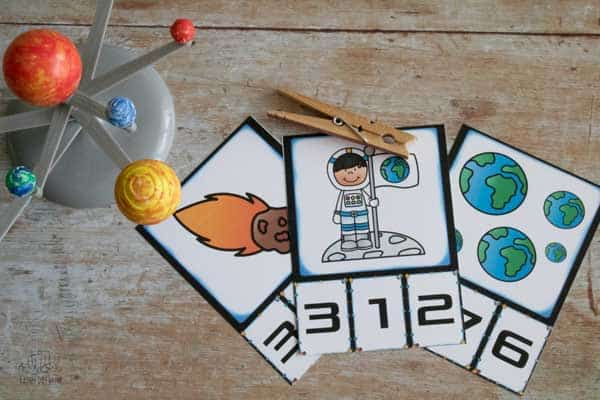 3 space themed count and clip cards with a peg and a model of the solar system