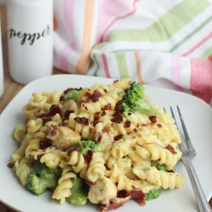 plate of bacon and chicken pasta with broccoli on a plate with a pepper pot behind and tea towel