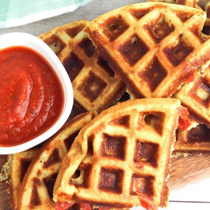 close up of dinner waffles with pepperoni and cheese with a pot of homemade pizza sauce on a wooden tray with a green tea towel behind