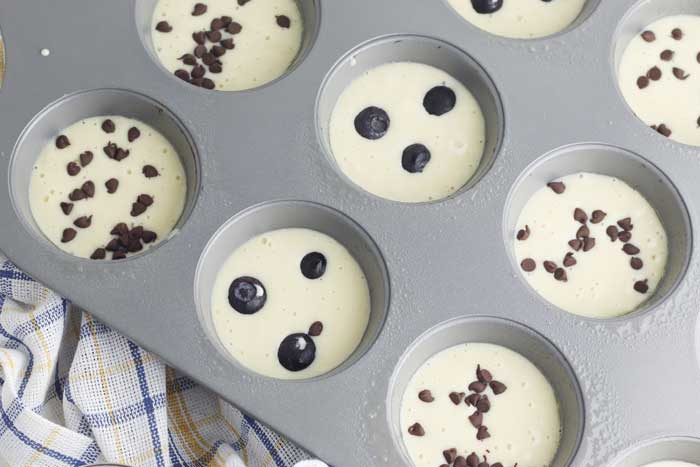 a mix of chocolate chip and blueberry pancake muffins ready to go in the oven to make in a muffin pan