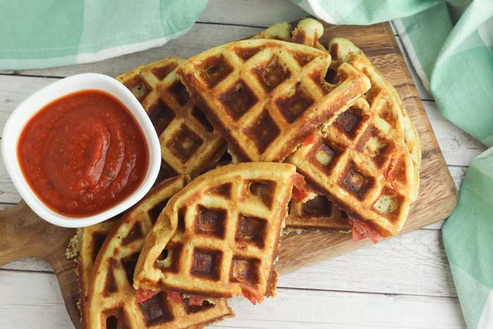waffle segments with pepperoni peeking out on a wooden chopping board with a pot of homemade pizza sauce and a mint green tea towel around the edge