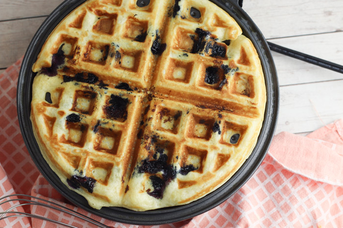 blueberry waffles on a waffle maker ready to serve