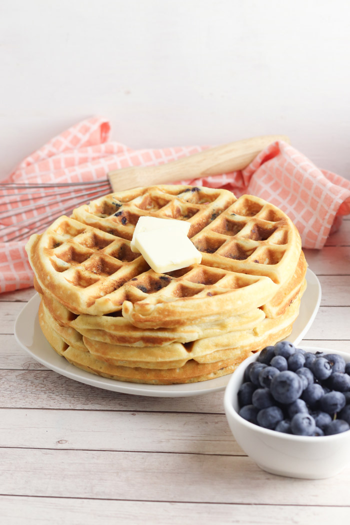 a stack of blueberry waffles with a bowl of blueberries beside ready to have maple syrup added for breakfast at the weekend