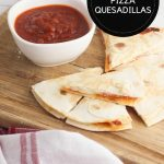 image created for pinterest of pizza quesadillas on a wooden chopping board with dipping sauce text in a black circle in upper right corner reads Pepperoni Pizza Quesadillas