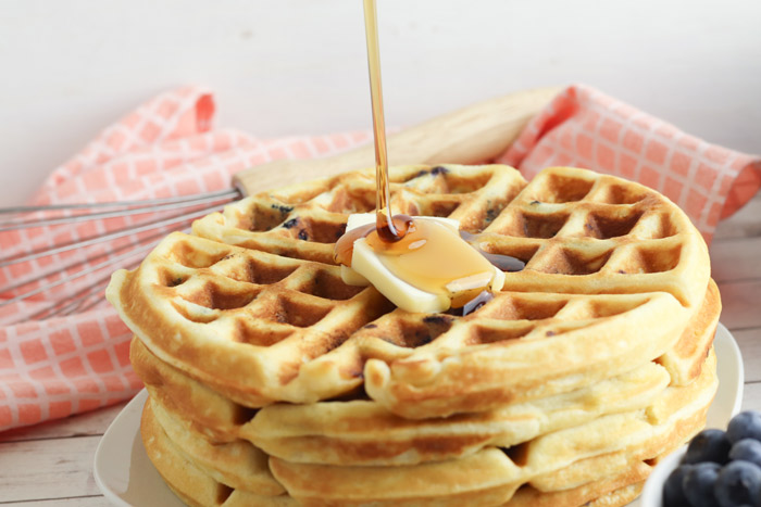 pouring maple syrup on a stack of blueberry waffles with butter on top