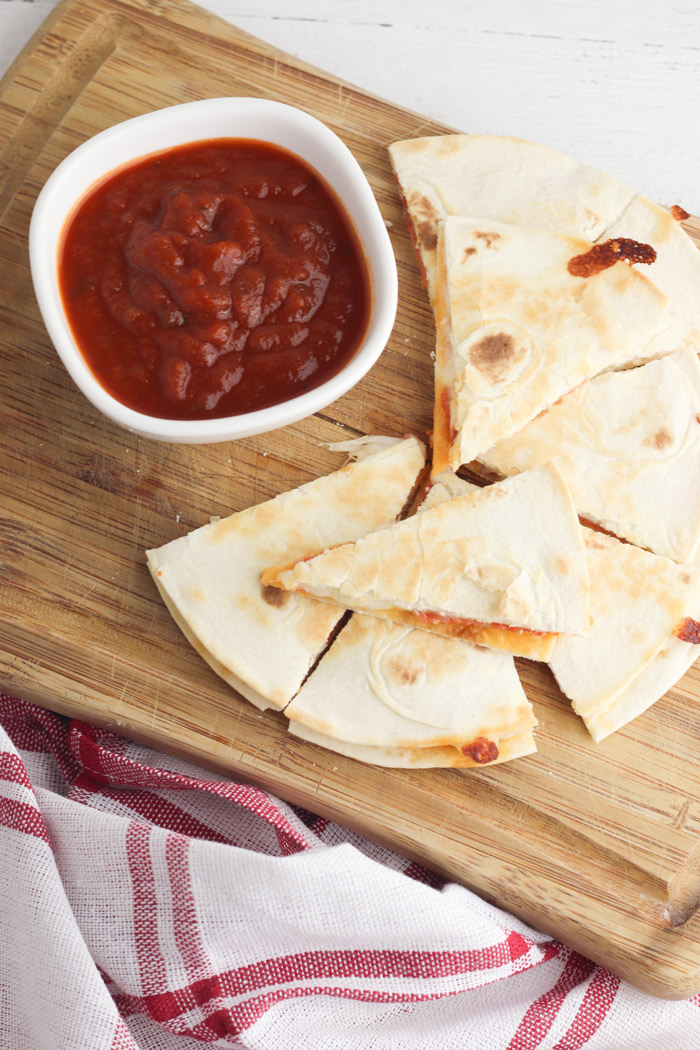 overhead view of a wooden chopping board with pizza quesadillas on and a bowl of tomato dipping sauce