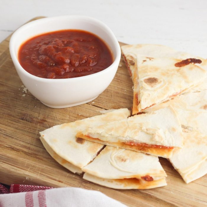 flour tortilla quesadillas filled with mozzarella and pepperoni sliced into eights on a wooden chopping board with pizza dipping sauce in a white finger bowl