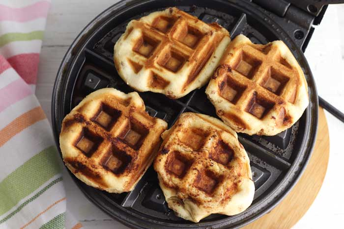 cinnamon roll waffles on the waffle iron
