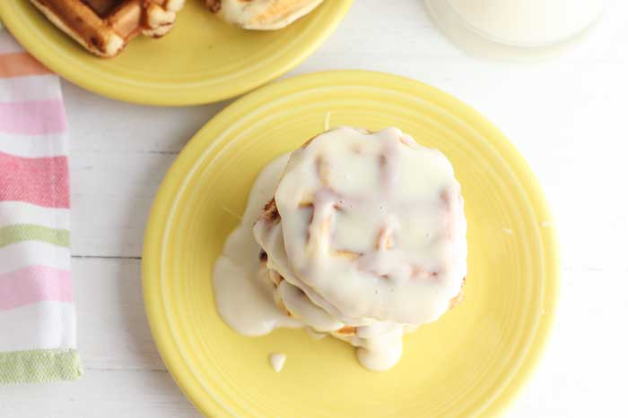 cinnamon roll waffles with cream cheese frosting drizzled on top