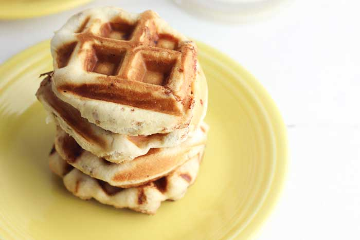 cinnamon roll waffles in a stack on the plate